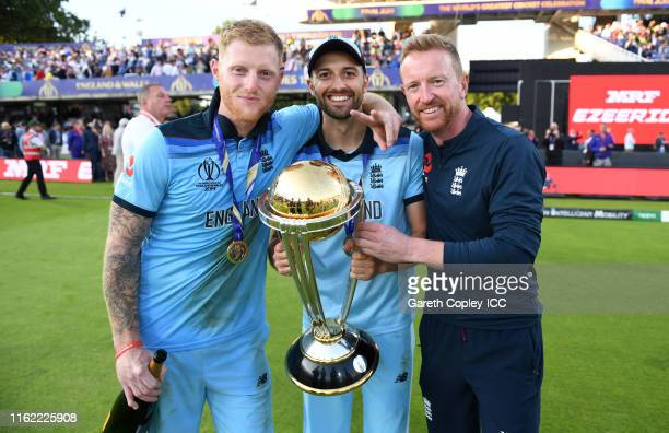 Ben Stokes and Mark Wood of England celebrates with coach Paul Collingwood and the trophy after winning the Final of the ICC Cricket World Cup 2019...