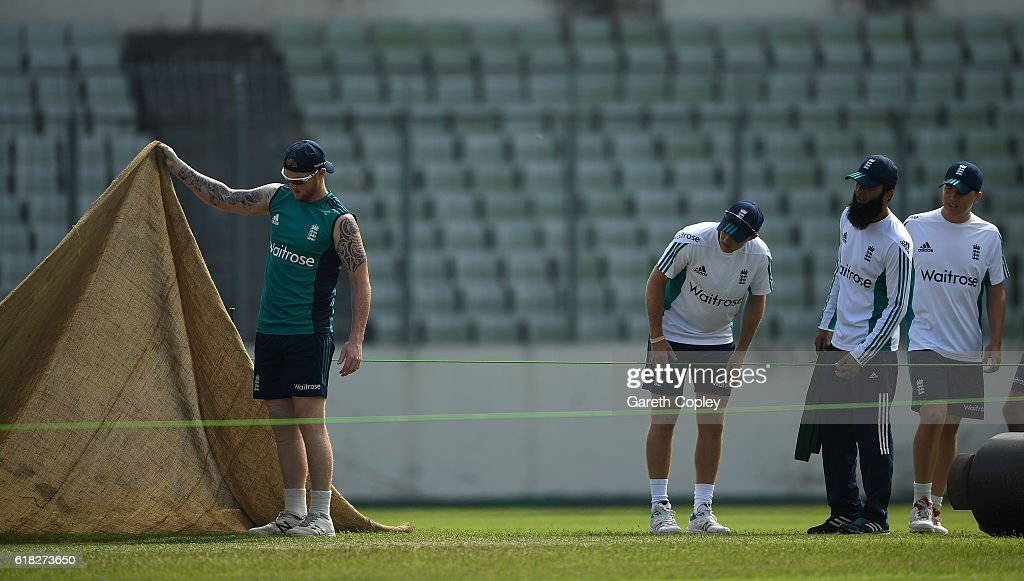 Ben Stokes, Joe Root, Moeen Ali and Gary Ballance of England try to get a look at the pitch ahead a nets session at Sher-e-Bangla National Cricket Stadium on October 26, 2016 in Dhaka, Bangladesh.