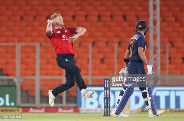 Ben Stokes of England bowls watched on by Virat Kohli of India during the 3rd T20 International between India and England at Narendra Modi Stadium on...