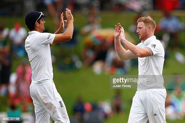 Ben Stokes of England celebrates taking the wicket of Hashim Amla of South Africa with Alastair Cook of England during day one of the 4th Test at...