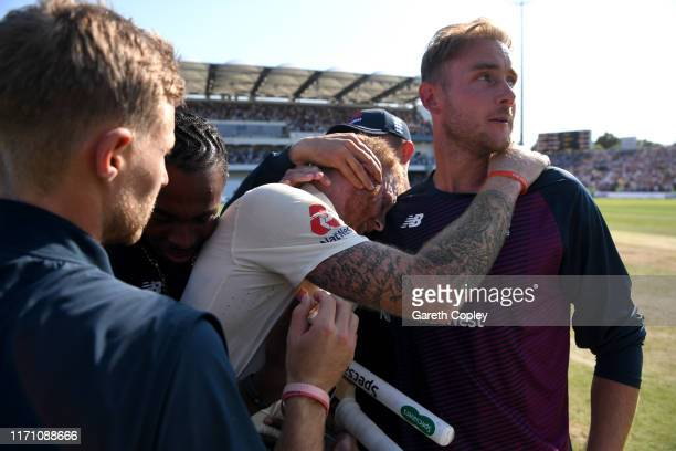 Ben Stokes of England celebrates with teammates Jason Roy Jofra Archer Joe Root and Stuart Broad after hitting the winning runs to win the 3rd...