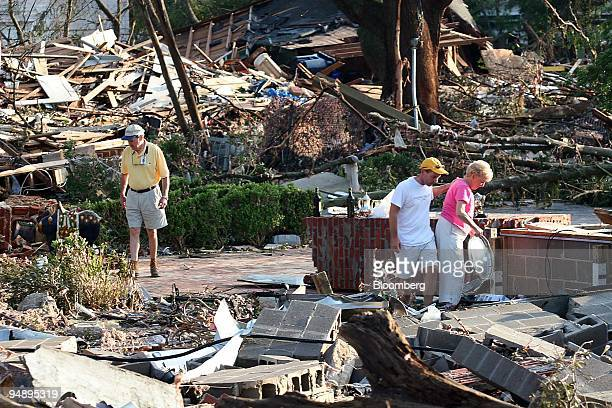 Ben Stone and his wife Nancy look through the remains of their home with their soninlaw Terry Robinson center after Hurricane Katrina destroyed their...