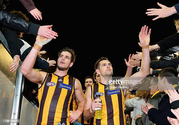 Ben Stratton and Luke Hodge of the Hawks high five fans after winning the round 21 AFL match between the Hawthorn Hawks and the Collingwood Magpies...
