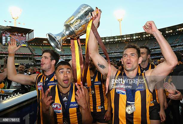 Ben Stratton Bradley Hill and Luke Hodge of the Hawks walk off the field with the Premeirship Cup during the 2014 AFL Grand Final match between the...