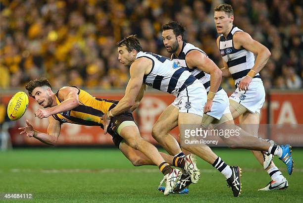 Ben Stratton of the Hawks handballs whilst being tackled by Corey Enright of the Cats during the AFL 2nd Qualifying Final match between the Hawthorn...