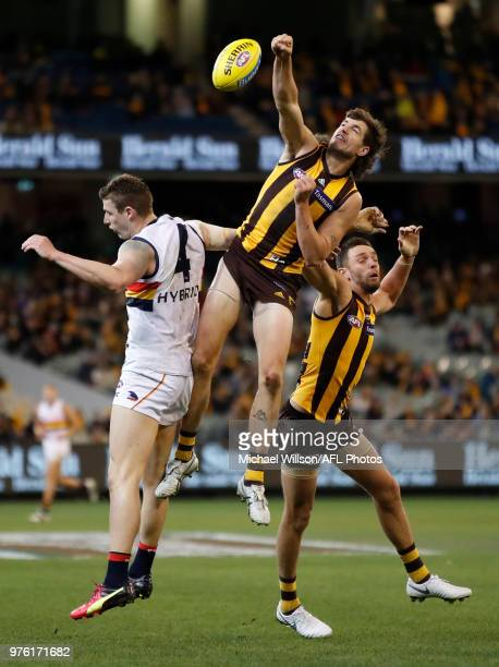 Ben Stratton of the Hawks punches the ball from Josh Jenkins of the Crows during the 2018 AFL round 13 match between the Hawthorn Hawks and the...