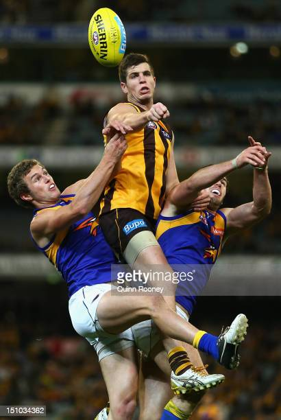Ben Stratton of the Hawks spoils a mark by Jacob Brennan and Jack Darling of the Eagles during the round 23 AFL match between the Hawthorn Hawks and...