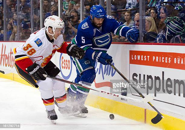 Ben Street of the Calgary Flames and Jason Garrison of the Vancouver Canucks battle for the puck in the corner during the first period in NHL action...