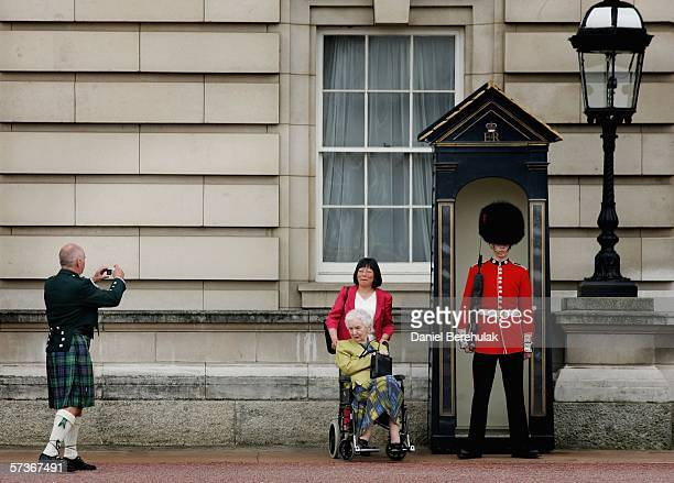 Ben Sutherland takes a photo of his mother Janet Sutherland and Yean Trailer with a Foot Guard of the Queen's Guard after their lunch at Buckingham...