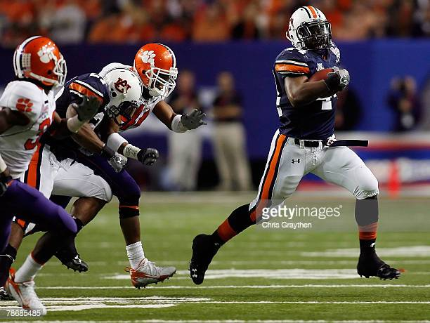 Ben Tate of the Auburn University Tigers tries to avoid a tackle by Chris Chancellor of the Clemson University Tigers during the ChickFilA Bowl on...