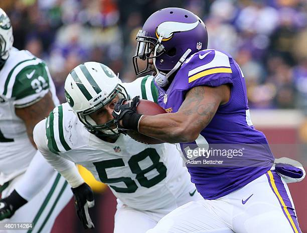 Ben Tate of the Minnesota Vikings carries the ball while Jason Babin of the New York Jets eyes the play in the fourth quarter on December 7 2014 at...