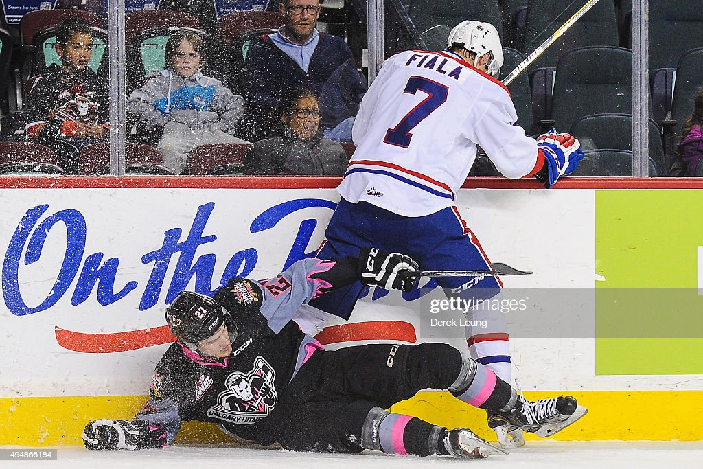 Ben Thomas #27 of the Calgary Hitmen gets checked by Evan Fiala #7 of the Spokane Chiefs during a WHL game at Scotiabank Saddledome on October 29, 2015 in Calgary, Alberta, Canada.