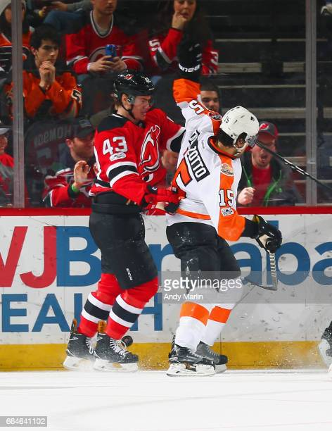 Ben Thomson of the New Jersey Devils playing in his first NHL game battles for position against Michael Del Zotto of the Philadelphia Flyers during...