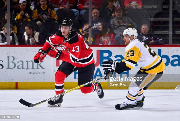Ben Thomson of the New Jersey Devils skates against Scott Wilson of the Pittsburgh Penguins during an NHL game at Prudential Center on April 6 2017...