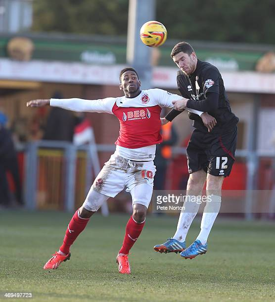 Ben Tozer of Northampton Town heads the ball away from Jamille Matt of Fleetwood Town during the Sky Bet League Two match between Fleetwood Town and...