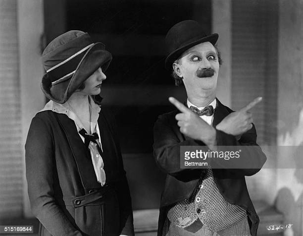 Ben Turpin American comedic actor giving a woman directions by crossing his eyes and pointing his hands in different directions Undated movie still
