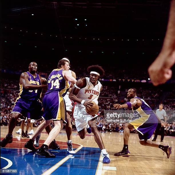Ben Wallace dribbles past Kobe Bryant and Stanislav Medvedenko of the Los Angeles Lakers during Game Five of the 2004 NBA Finals on June 15 2004 at...