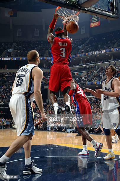 Ben Wallace of the Detroit Pistons dunks the ball while Brian Cardinal of the Memphis Grizzlies looks on during a game between the Detroit Pistons...