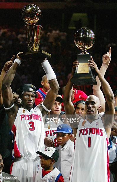 Ben Wallace of the Detroit Pistons holds up the Larry O'Brien NBA Championship as teammate Chauncey Billups holds the MVP trophy after defeating the...