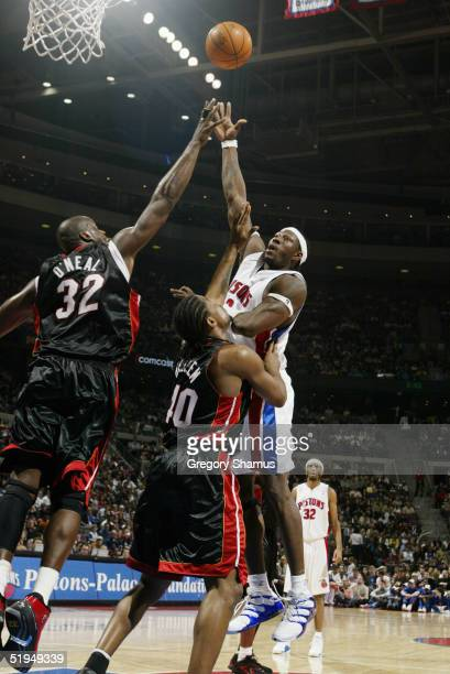 Ben Wallace of the Detroit Pistons shoots over Udonis Haslem and Shaquille O'Neal of the Miami Heat during the game at the Palace of Auburn Hills on...