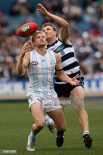 Ben Warren of the Kangaroos attempts to mark as Darren Milburn of the Cats spoils during the round 14 AFL match between the Geelong Cats and the...