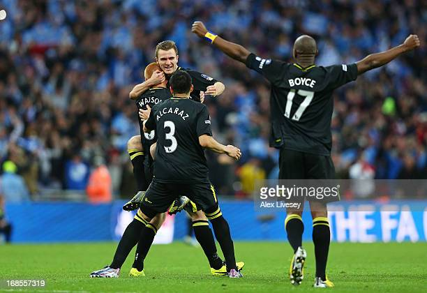 Ben Watson Callum McManaman Antolin Alcaraz and Emmerson Boyce of Wigan Athletic celebrate victory after the FA Cup with Budweiser Final between...
