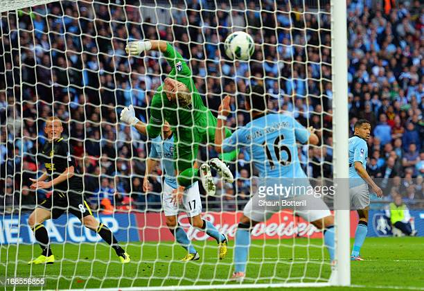 Ben Watson of Wigan Athletic heads the ball past Joe Hart of Manchester City to score their first goal during the FA Cup with Budweiser Final between...