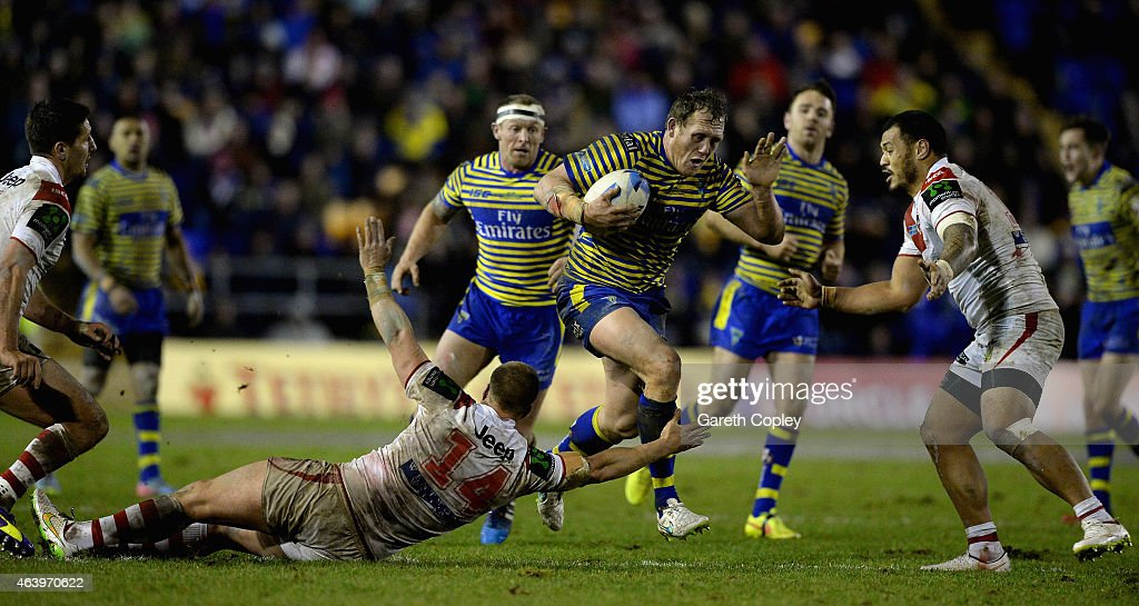 Ben Westwood of Warrington Wolves jumps through a tackle from Trent Merrin of St George Illawarra Dragons during the World Club Series match between Warrington Wolves and St George Illawarra Dragons at The Halliwell Jones Stadium on February 20, 2015 in Warrington, England.