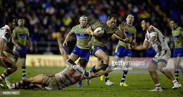 Ben Westwood of Warrington Wolves jumps through a tackle from Trent Merrin of St George Illawarra Dragons during the World Club Series match between...