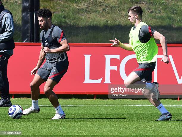 Ben Woodburn and Alex Oxlade-Chamberlain of Liverpool during a training session at AXA Training Centre on April 22, 2021 in Kirkby, England.
