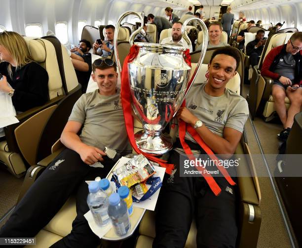 Ben Woodburn and Trent AlexanderArnold of Liverpool with the UEFA Champions League trophy during the flight home from winning the UEFA Champions...
