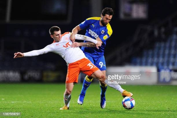 Ben Woodburn of Blackpool battles for possession with Ollie Palmer of AFC Wimbledon during the Sky Bet League One match between AFC Wimbledon and...