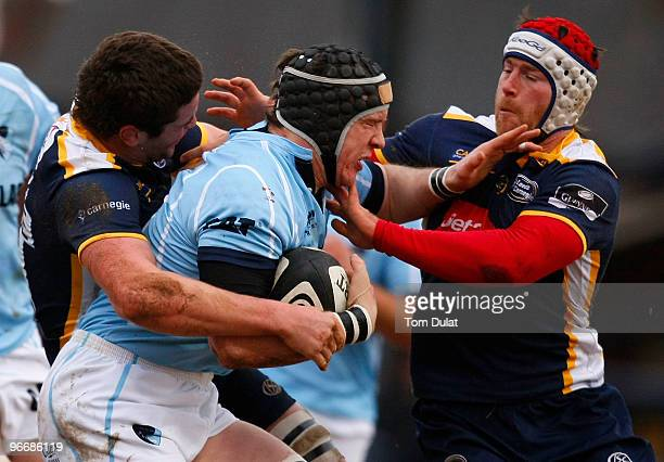 Ben Woods of Leicester Tigers is challenged by Calum Clark and Andy Titterrell of Leeds Carnegie during the Guinness Premiership match between Leeds...