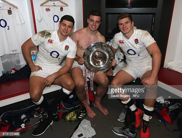 Ben Youngs George Ford and Owen Farrell of England pose with the Triple Crown trophy in the dressing room after the RBS Six Nations match between...