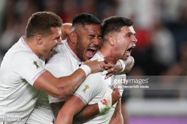 Ben Youngs of England celebrates with team mates Manu Tuilagi and Henry Slade after scoring his side's second try which was later disallowed during...
