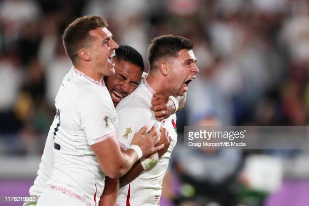 Ben Youngs of England celebrates with team mates Manu Tuilagi and Henry Slade after scoring his side's second try, which was later disallowed during...