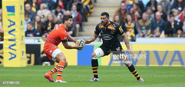 Ben Youngs of Leicester passes the ball watched by Andrea Masi during the Aviva Premiership match between Wasps and Leicester Tigers at The Ricoh...