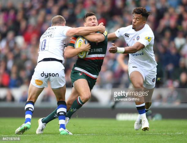 Ben Youngs of Leicester Tigers is tackled by Rhys Priestland and Anthony Watson of Bath Rugy during the Aviva Premiership match between Leicester...