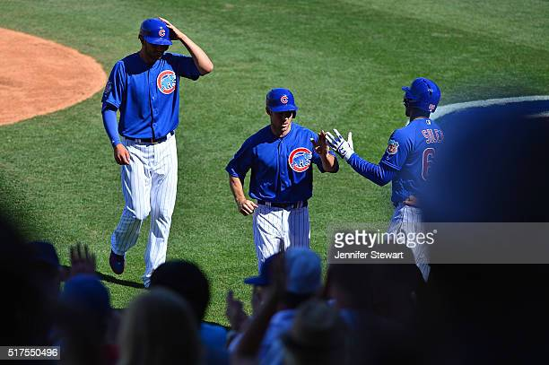 Ben Zobrist and Kris Bryant of the Chicago Cubs score in the sixth inning against the Milwaukee Brewers during the spring training game at Sloan Park...