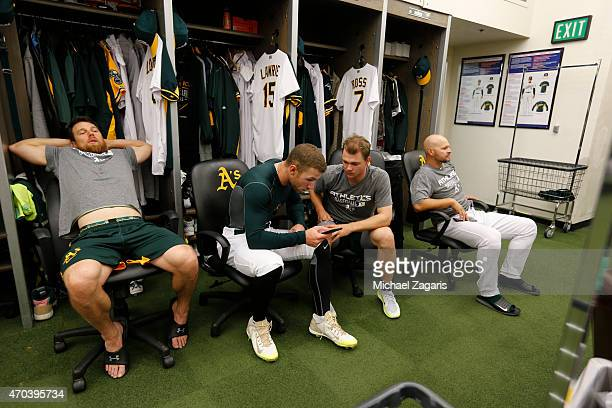 Ben Zobrist Brett Lawrie Sonny Gray and Cody Ross of the Oakland Athletics relax in the clubhouse prior to the game against the Texas Rangers at Oco...