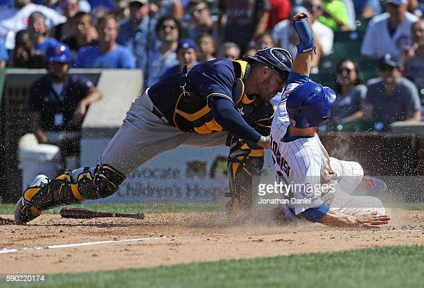 Ben Zobrist of the Chicago Cubs beats the tag by Manny Pina of the Milwaukee Brewers to score a run in the 8th inning at Wrigley Field on August 16...