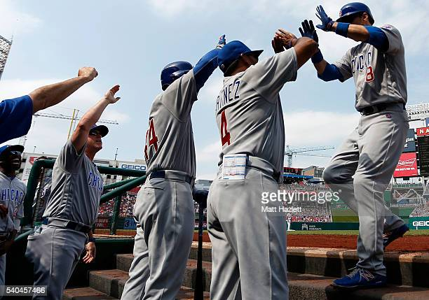 Ben Zobrist of the Chicago Cubs celebrates with teammates Dave Martinez and Anthony Rizzo after hitting a first inning home run against the...