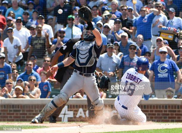 Ben Zobrist of the Chicago Cubs is safe at hone as Austin Hedges of the San Diego Padres takes a late throw during the second inning on August 4,...