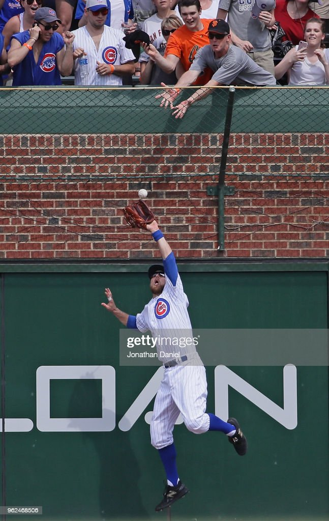 Ben Zobrist #18 of the Chicago Cubs leps to make a catch at the wall on a ball hit by Brandon Belt of the San Francisco Giants in the 6th inning at Wrigley Field on May 25, 2018 in Chicago, Illinois.