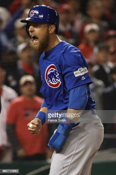 Ben Zobrist of the Chicago Cubs reacts after scoring on a double hit by Addison Russell of the Chicago Cubs against the Washington Nationals during...