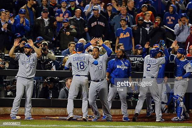 Ben Zobrist of the Kansas City Royals celebrates with his teammates after scoring a run off of a three run RBI double hit by Lorenzo Cain to also...