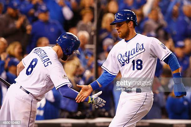 Ben Zobrist of the Kansas City Royals high fives Mike Moustakas of the Kansas City Royals after scoring a run in the eighth inning against the...