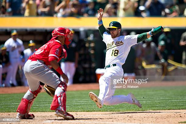 Ben Zobrist of the Oakland Athletics slides past Carlos Perez of the Los Angeles Angels of Anaheim to score a run during the sixth inning at Oco...