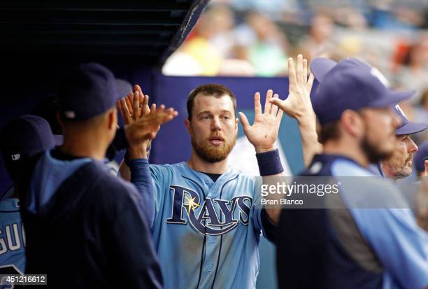 Ben Zobrist of the Tampa Bay Rays celebrates in the dugout after scoring off a single by James Loney of the Tampa Bay Rays during the eighth inning...