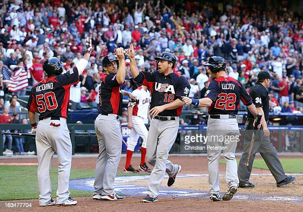 Ben Zobrist of USA highfives David Wright Shane Victorino and Jonathan Lucroy after scoring against Canada during the ninth inning of the World...